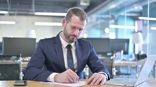 Thumbnail for Young Businessman Writing Documents on Office Desk