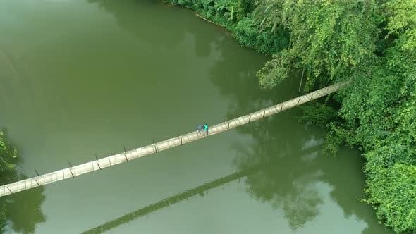 Cover Image for Villagers Walking On A Suspension Bridge