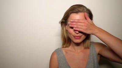 Blonde Model Doing the Peek-A-Boo Gesture