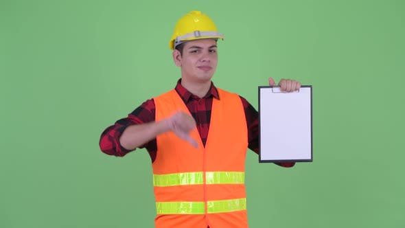 Thumbnail for Stressed Young Multi Ethnic Man Construction Worker Showing Clipboard and Giving Thumbs Down