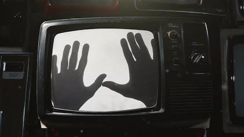 Geisterhafte Hände erscheinen auf dem flackernden Bildschirm eines alten Fernsehgeräts. 4K-Version.