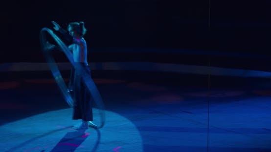 Thumbnail for Zirkus-Darsteller steht auf der Bühne unter dem Rampenlicht und dreht den Reifen