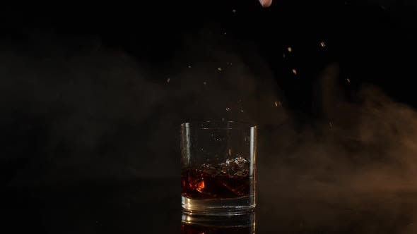 Barman Dropping Ice Cubes Into Drinking Glass with Golden Whiskey Cognac Brandy on Black Background