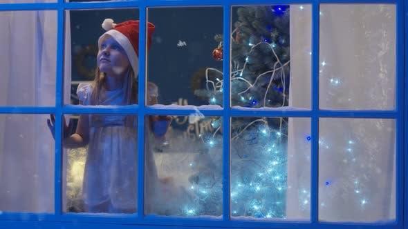 Thumbnail for Charming Girl Through Window in Santa Hat