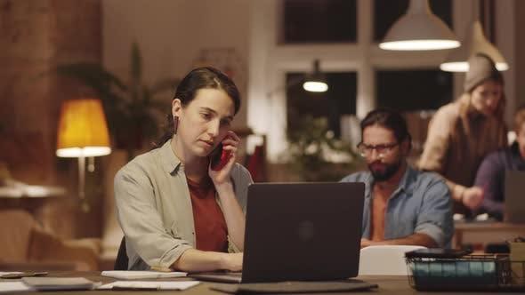 Thumbnail for Frau spricht am Telefon und arbeitet am Laptop im Büro