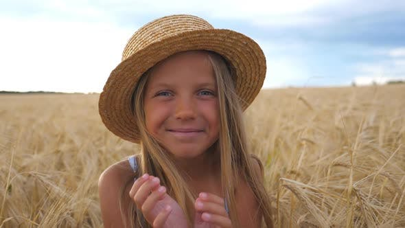 Thumbnail for Beautiful Smiling Girl in Straw Hat Looking Into Camera Against the Background of Barley Field at