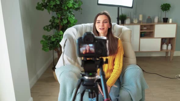 Beautiful Girl Blogger in Yellow Sweater is Filming Her Blog on Camera at Home