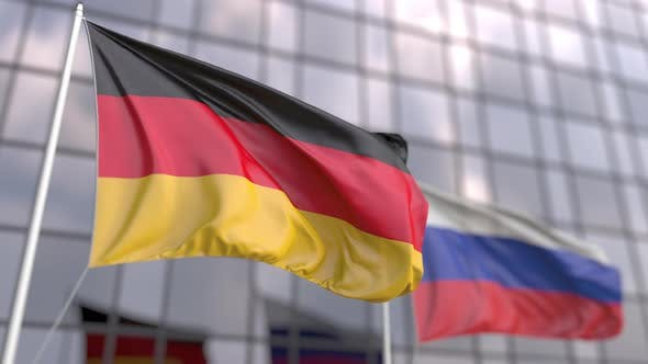 Waving Flags of Germany and Russia in Front of a Skyscraper