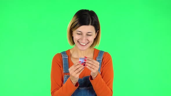 Thumbnail for Girl Opens a Small Box with a Surprise and Is Very Disappointed with What She Saw. Green Screen
