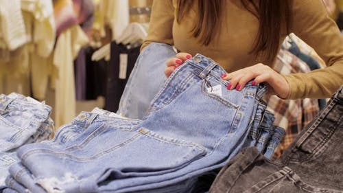 Lady Chooses Appropriate Size of Blue Denim Jeans with Sales