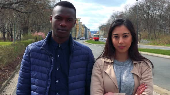 Thumbnail for A Young Black Man and a Young Asian Woman Shake Their Heads at the Camera in a Street in Urban Area