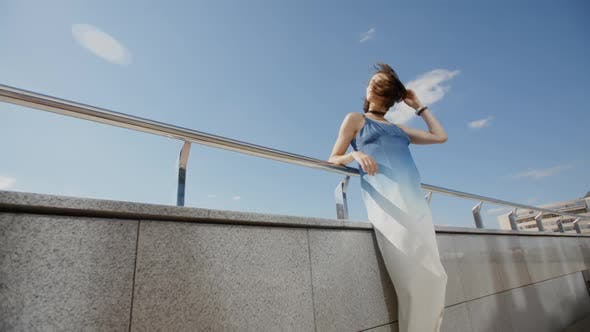 Thumbnail for Beautiful Girl In Long Dress Posing In The Wind In City Street