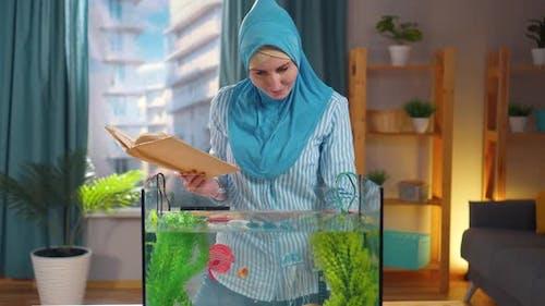 Muslim Woman in National Headscarf Studies a Book on Aquariums and Feeds Goldfish in an Aquarium