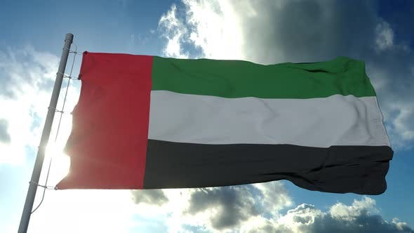 Flag of the United Arab Emirates Waving in the Air Cloudy Blue Sky in Background