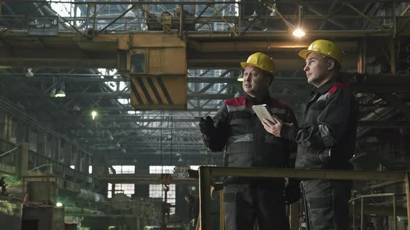 Tractor Plant Workers Having Conversation
