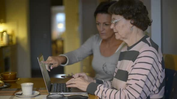 Daughter Teaching Her Mother in Using Laptop and Making Mistake