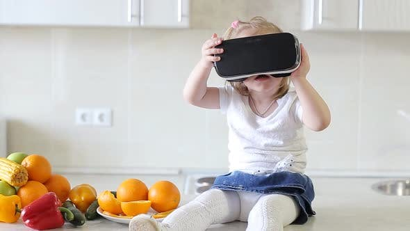 Thumbnail for UFA, RUSSIA - APRIL, 2017: Little Girl Uses a Virtual Reality Glasses in The Kitchen.