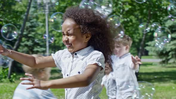 Cover Image for Happy African Girl Catching Soap Bubbles at Kids Party in Park