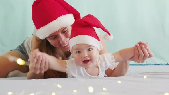 Thumbnail for Smiling Santa Child Lying in Santa Claus Costume, in Red Hat with Mother.