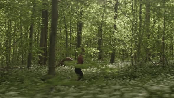 Lush Green Forest Surrounded By Plants and Trees and a Woman Running Fast