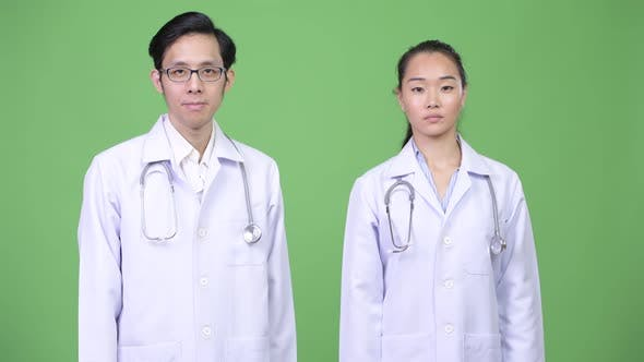Young Asian Couple Doctors Giving Handshake Together