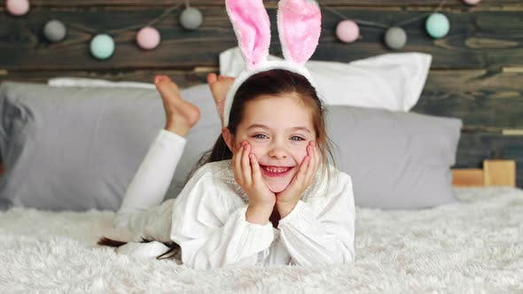 Smiling girl with bunny ears lying on the bed