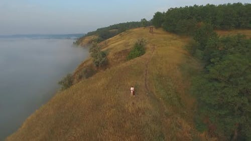 Aerial Shot of Beautiful Landscape in Early Morning. Young Couple Standing on Top of Hill and