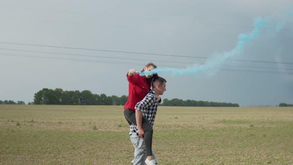 Man Piggybacking Woman with Smoke Bomb in Countryside