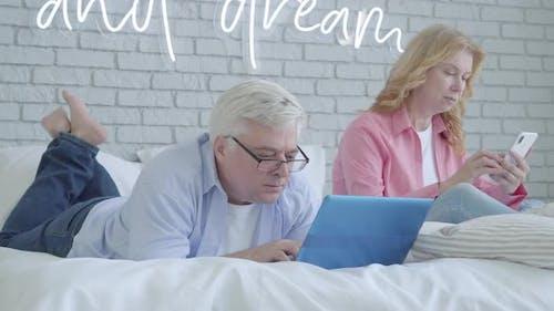 Nervous Mid-adult Man Gaming Online Ignoring Wife. Portrait of Engrossed Caucasian Senior Gamer