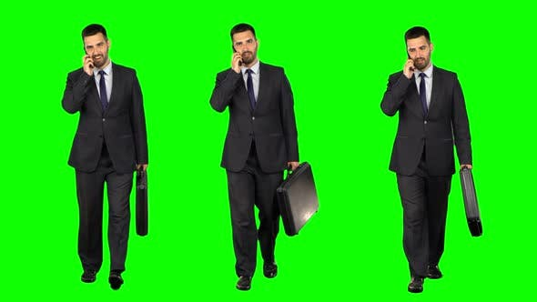 Thumbnail for Happy Young Businessman with a Suitcase Talking on Smartphone on Green Background, Chroma Key. Three