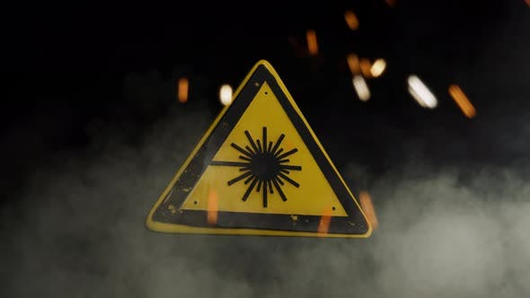 Laser Hazard Sign Over a Smoky Background