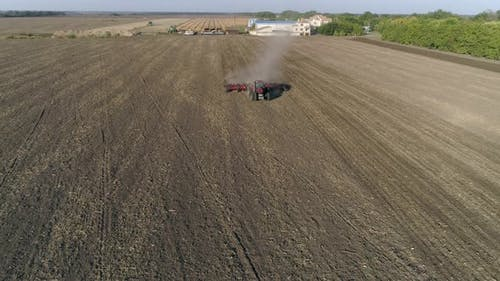 Farm Tractor with Plough Cultivates Agrarian Land on Field Before Sowing Agricultural Crops