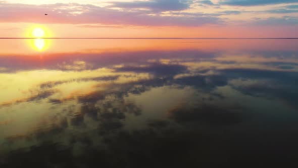 Cover Image for Aerial View of a Calm Clean Lake with a Mirror Surface Reflects the Sun