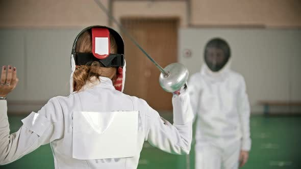 Thumbnail for Two Young Women Fencers Having a Training in the Gym - a Woman Stretches with the Sword Behind Her
