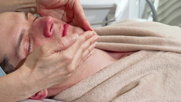 Thumbnail for Sliding Shot of a Man Relaxing at Spa, Receiving Face and Head Massage