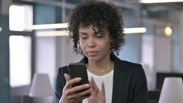 Thumbnail for Portrait of Shocked African Businesswoman Reacting To Loss on Smartphone