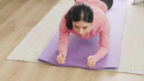 Asian woman doing yoga plank position at home during COVID-19 pandemic.