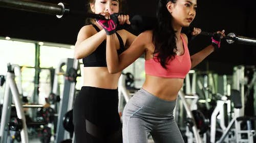 Asian Personal Trainer Coaching a Bodybuilding Woman to Perform Exercise Squats with Barbell in Gym