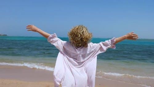 Woman Opening Arms On Beach Enjoying Sea, Aspirational Travel Lifestyle.