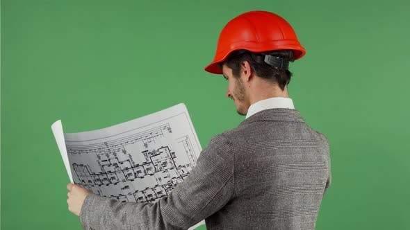Thumbnail for Handsome Bearded Engineer Smiling To the Camera While Examining Blueprints