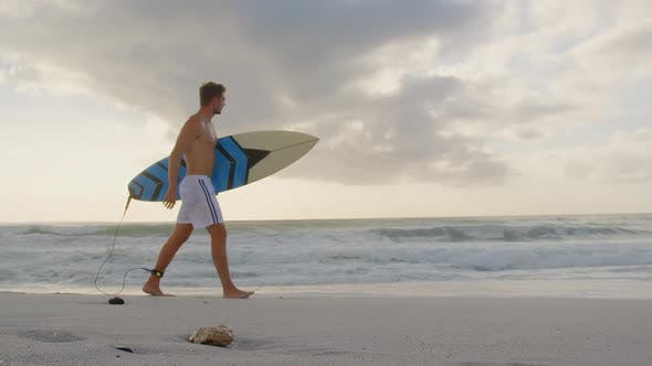 Man walking with surfboard at beach