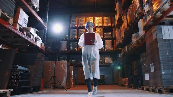 Pretty Young Lady Walking Between Shelves in Huge Storage Room and Making Notes During Inspection in
