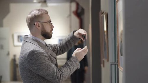 Man Taking Picture of Artwork with Smartphone in Gallery