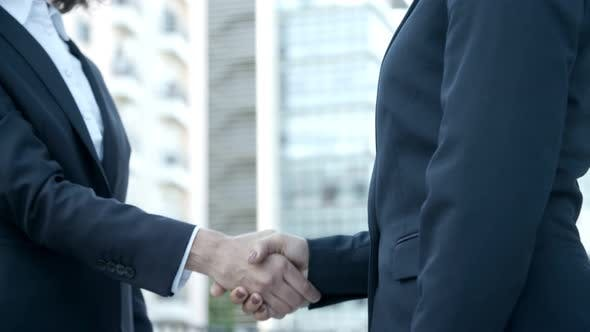 Cover Image for Two Businesswomen Shaking Hands on Street