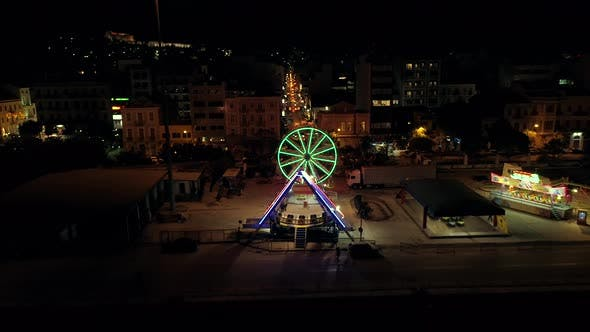 Aerial view of small amusement park with lights at night in Greece.