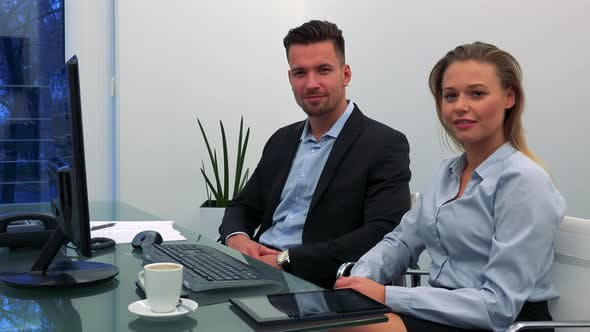 Thumbnail for Ein Mann und eine Frau (jung und attraktiv) sitzen an einem Schreibtisch in einem Büro und lächeln bei der Kamera