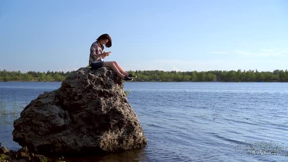 Cover Image for A Young Woman Sits on a Stone By the River with a Phone in Her Hands. The Girl Is Texting in the