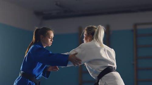 Sparring Girls auf der Tatami, Üben Sie Wrestling, Training im Fitnessstudio