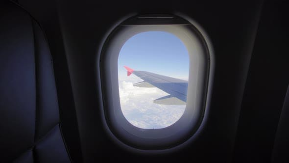Thumbnail for Airplane Flight. Wing of an Airplane Flying Above the Clouds. View From the Window of the Plane