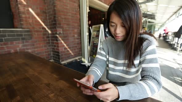 Thumbnail for Woman using smartphone in cafe